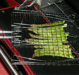 Asparagus grilling in a fish BBQ cage